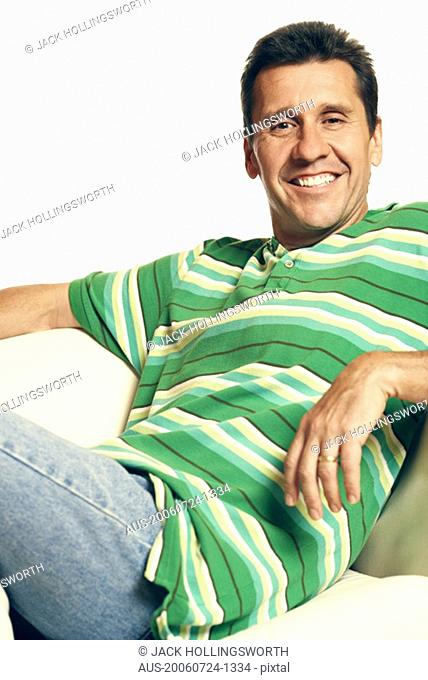Portrait of a mature man reclining on a couch and smiling