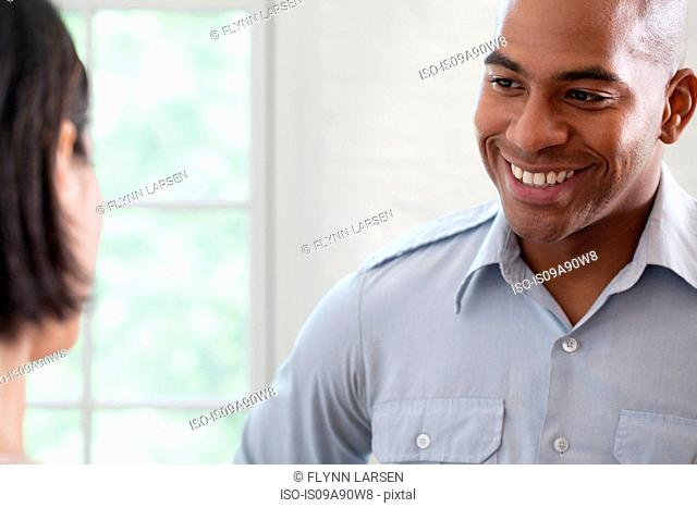 Mid adult man smiling at colleague