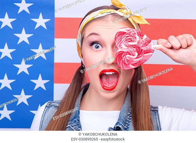 Waist up portrait of cheerful young woman holding a lollipop in shape of heart. She is covering her eye with it and shouting with shock