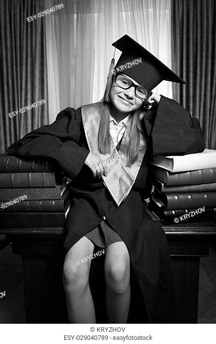 Black and white portrait of smart girl in graduation cap posing on table at library