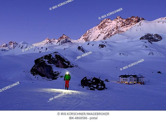 Ski tourer with headlamp in front of Heidelberger Hütte, dawn, Silvretta, Graubünden, Switzerland