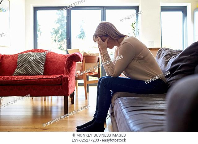 Depressed Mature Woman Sitting On Sofa At Home