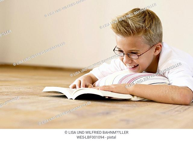 Smiling boy lying on wooden floor reading a book