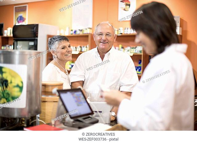 Senior couple paying in health shop