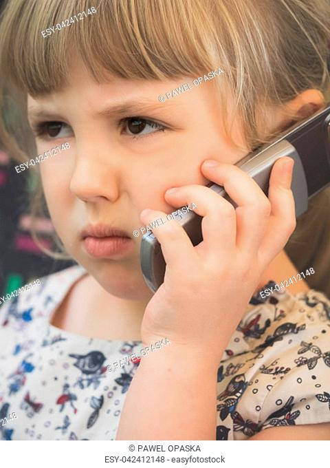 Cute little Caucasian girl talking on the mobile phone while sitting in the train carriage