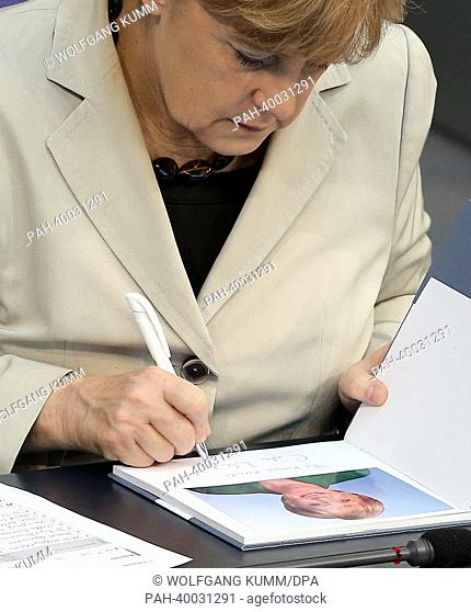 Chancellor Angela Merkel (CDU) signs a book in the German Bundestag in Berlin, Germany, 06 June 2013. The Bundestag debates the situation of the municipalities...