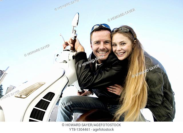 Couple sitting on a motor scooter and smiling