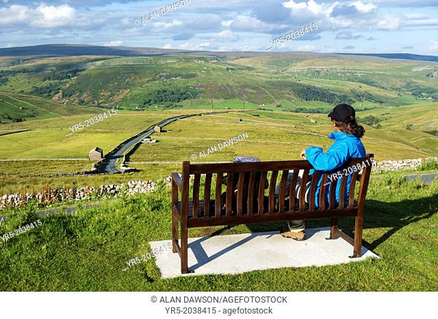 Female hiker on seat overlooking Buttertubs pass in The Yorkshire Dales National Park. Yorkshire, England, UK. View over Buttertubs pass