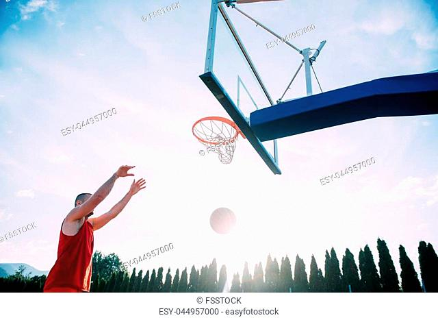 Young man jumping and making a fantastic slam dunk playing streetball, basketball. Urban authentic