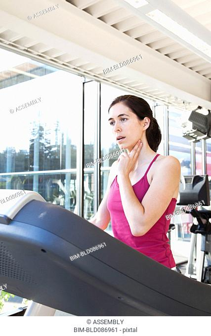 Woman on treadmill checking her pulse