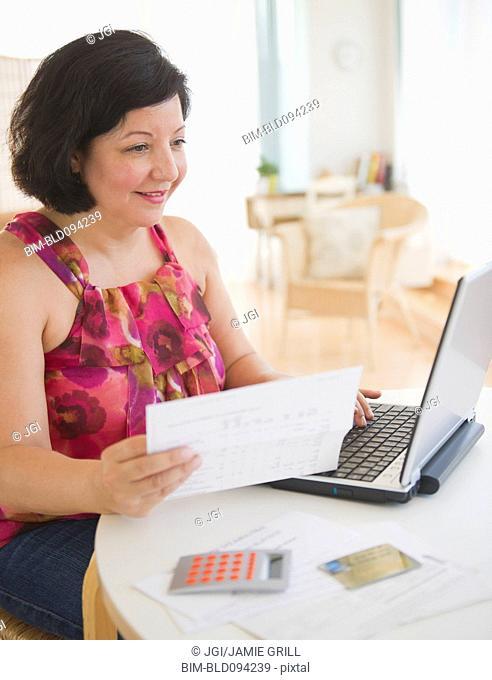 Hispanic woman holding paper and using laptop