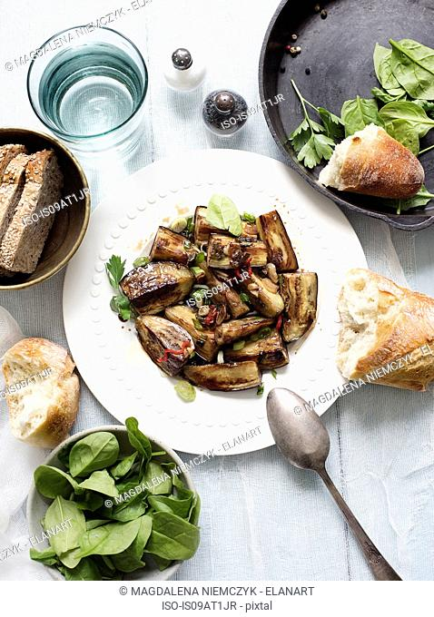 Still life of plate of fried aubergines with garnish and spinach
