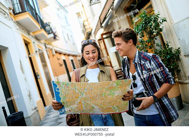 Happy young couple with city map and camera on an alley
