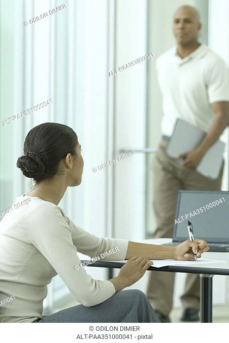 Female office worker looking up as man enters