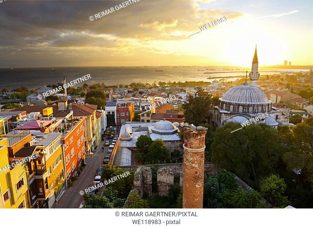 Setting sun behind the Sokollu Mehmet Pasha mosque minaret with golden glow on houses and Marmara Sea Istanbul