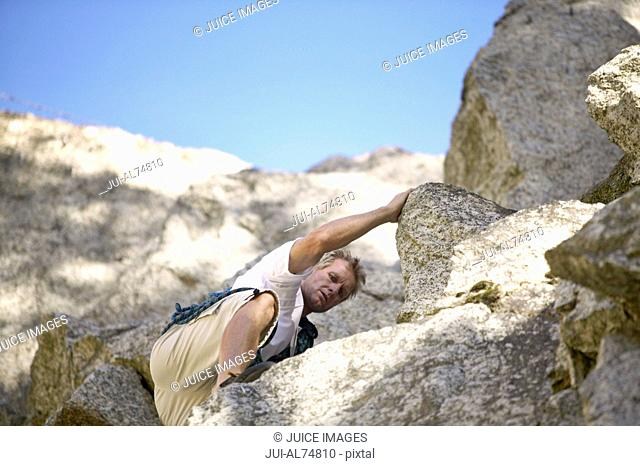View of a middle aged man rock climbing