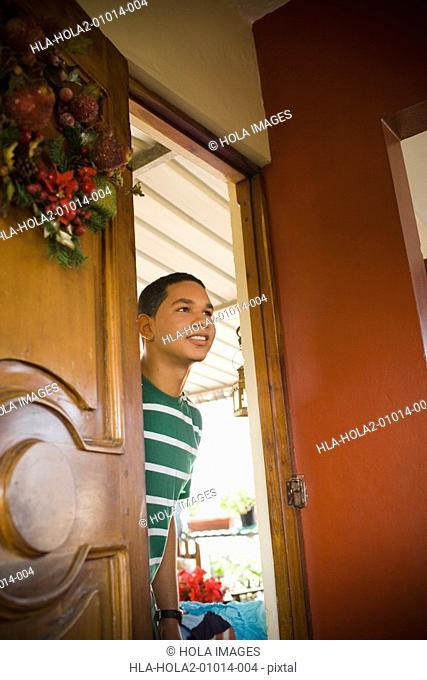 Young man peeking through a door