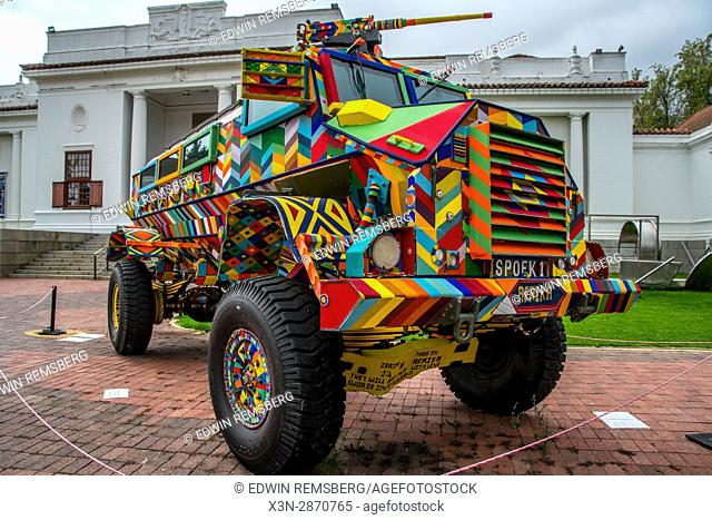 A military tank beaded with intricate geometric designs and vibrant colors is displayed in front of the South African National Gallery, located in Cape Town