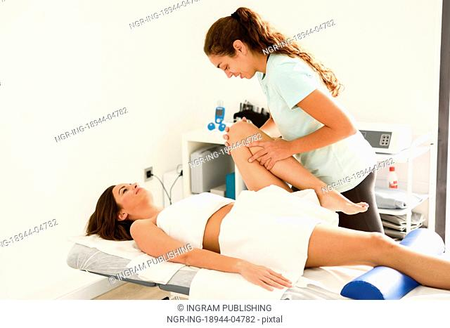 Medical massage at the leg in a physiotherapy center. Female physiotherapist inspecting her patient