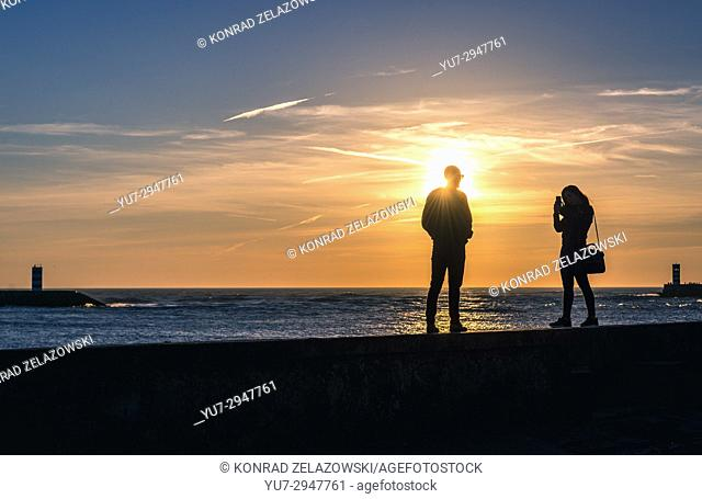 Couple walks on a boardwalk in Foz do Douro district of Porto city, second largest city in Portugal