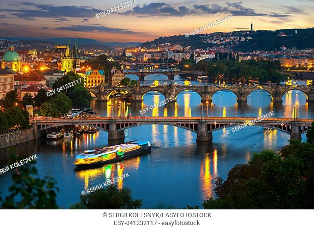 Illuminated bridges in Prague on river Vltava at sunset