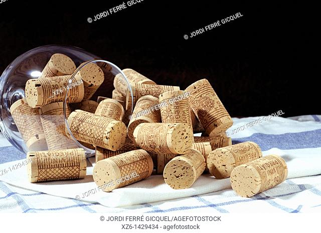 corks in a glass and pile of corks