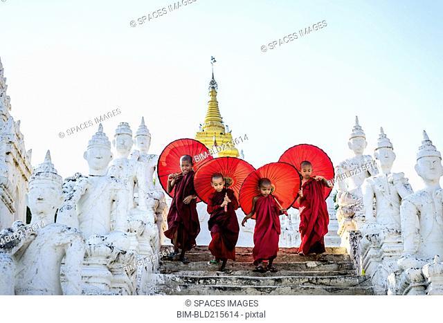 Asian children with parasols balancing on Buddhist shrine
