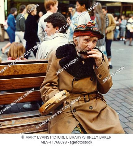 Elderly man playing harmonica and tambourine, sitting on a bench in a street