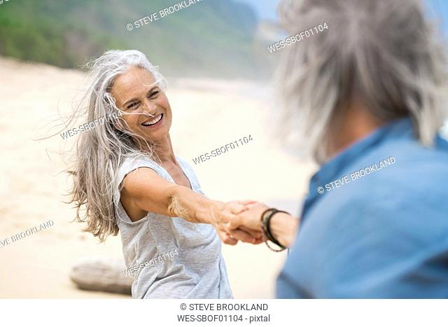 Handsome senior couple dancing on the beach