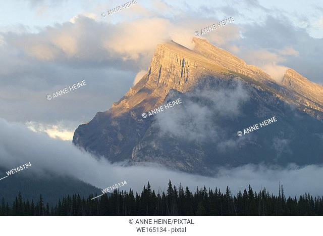 Scenic Mount Rundle in Banff National Park next to the city of Banff. Appearing out of clouds, and the peak is illuminated by the last sunlight