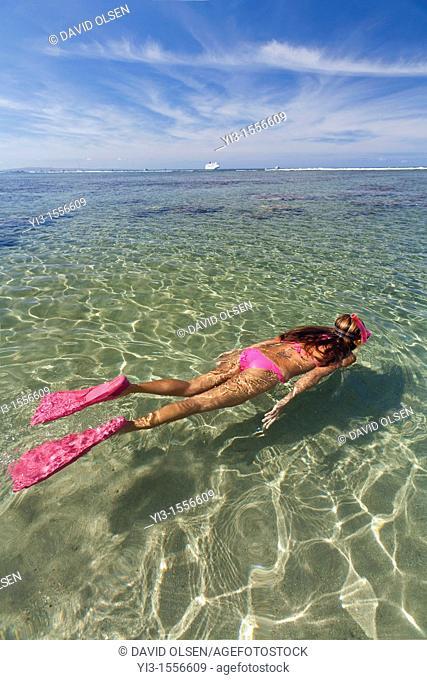 Woman in pink bikini heads out to go snorkeling in Lahaina, Maui, Hawaii