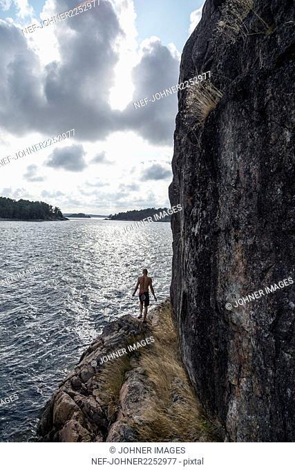Man walking on rocky coast