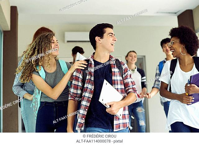 Students laughing as they walk together on campus
