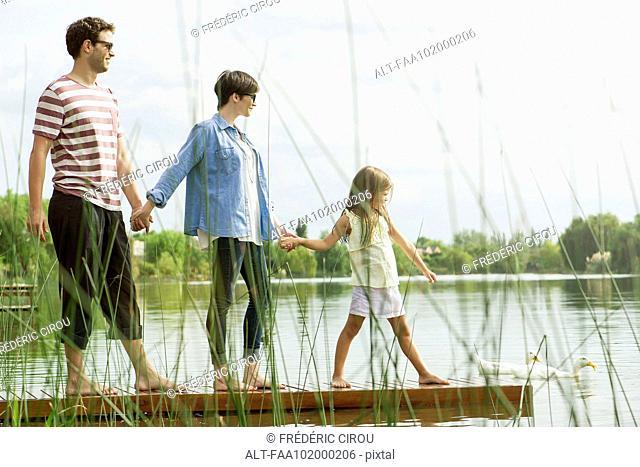 Family holding hands on dock