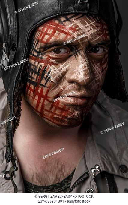 Portrait of Brutal Man with Creative Military Style Camouflage. Face Paint. Close up on black background