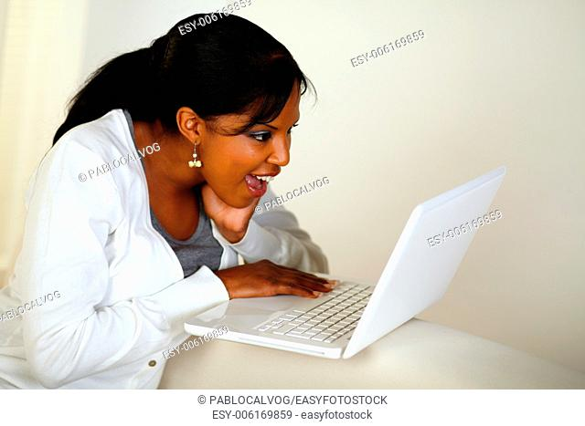 Portrait of a surprised young woman reading a message on laptop screen