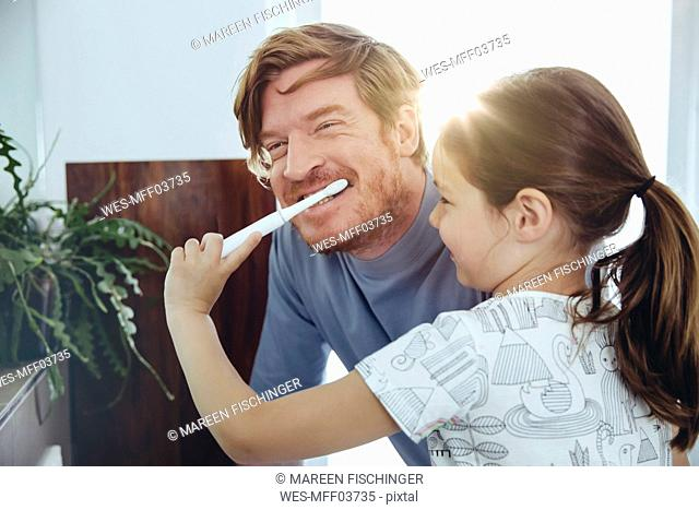 Daughter brushing her father's teeth in bathroom