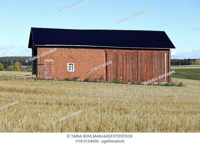 Old red farm building on stubble field with blue sky background on a beautiful day of autumn in Paimio, Finland. October 6, 2018