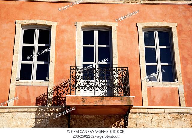 Facade of a old building with balcony at the Venetian harbor near the sea, Chania, Crete, Greek Islands; Greece, Europe