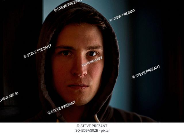 Portrait of intimidating young man wearing hood in shadows