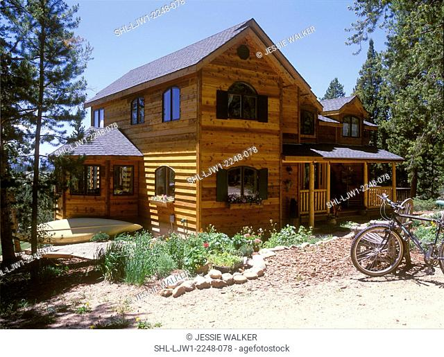 EXTERIOR - View 1. Colorado cabin with clapboard siding and log accents, green shutters, angle shot, bicycles, kayak, sunroom juts out from two story house