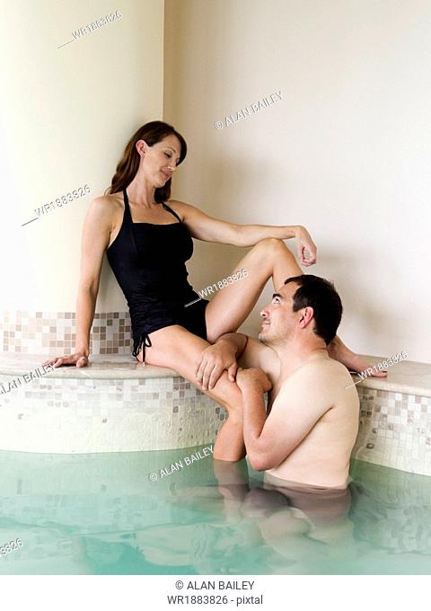 Italy, Tuscany, Couple relaxing in swimming pool