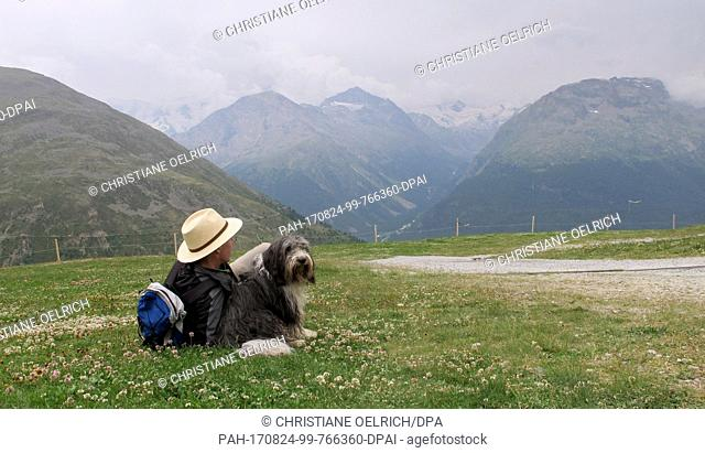 A hiker and his dog resting in Muottas Muragl - a good 2500 meters high - in the canton of Graubunden, Switzerland, 20 July 2017