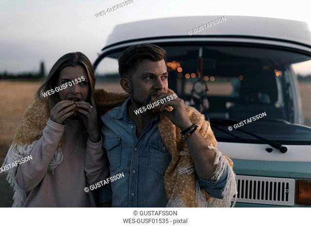 Couple wrapped in a blanket at camper van having a snack in rural landscape