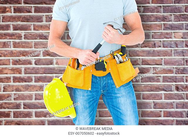 Composite image of worker holding hammer over white background