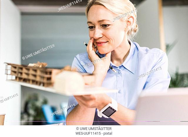 Woman in office holding architectural model