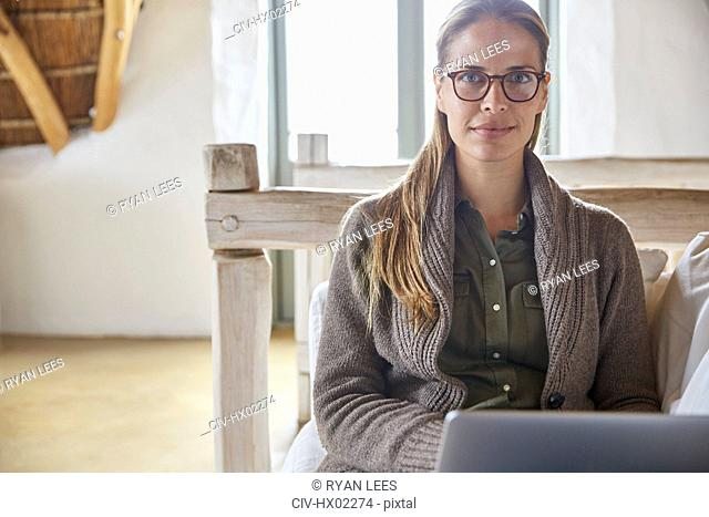 Portrait confident woman using laptop on sofa