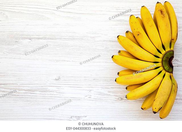 Bunch of baby banana on white wooden background, top view. Copy space