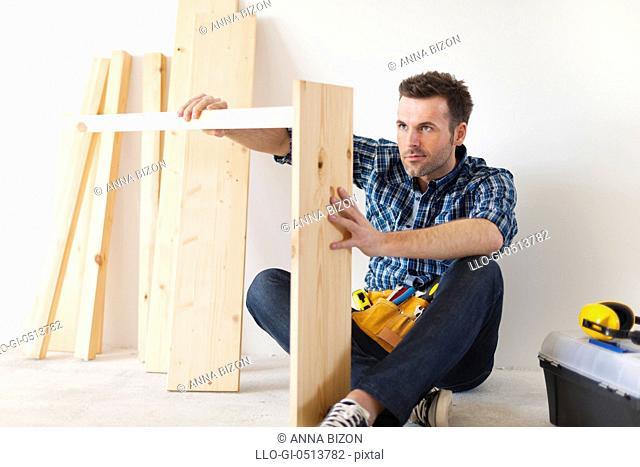 Handsome carpenter working on new furniture. Pilzno, Poland