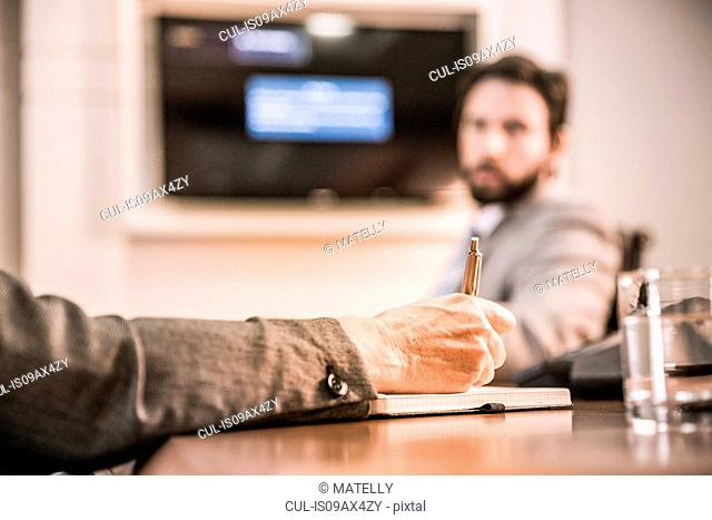 Cropped view of womans hand writing in notebook in business meeting